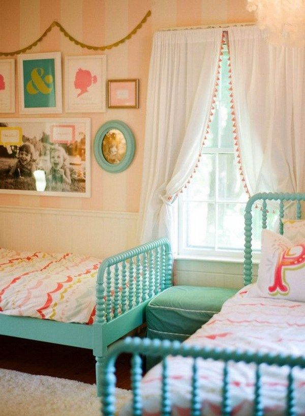 Girly shared bedroom decorating ideas with turquoise beds and pom-pom trimmed curtains.