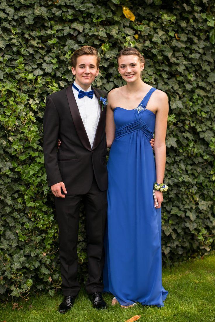 Homme en un smoking et femme en une robe de bal longue bleu asymétrique