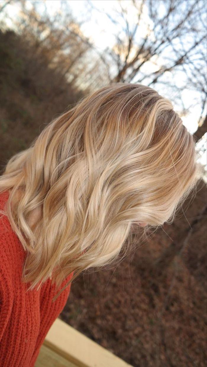 ein Mädchen mit rotem Pullover, schulterlange Haare, ein Etage Schnitt hellbrau…