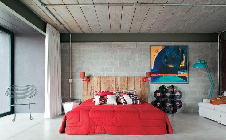 Pendentes, arandelas e interruptores estão conectados por meio de tubulação galvanizada aparente. Para que a claridade não atrapalhe o sono, cortinas blecaute, da Castelo da Cortina, correm em trilhos ao longo de toda a janela frontal da casa. A luminária azul de piso dá um toque retrô, assim como o aparador criado pelo próprio arquiteto com discos de vinil.