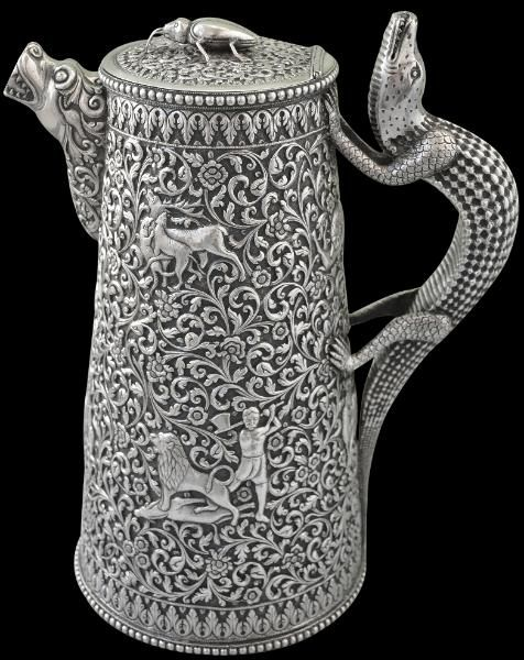 This rather extraordinary and monumental solid silver water jug with tapering sides is profusely decorated all over with typically Cutch chasing work. The sides feature an elephant in combat with a lion; a pair of monkeys; a lion attacking a fallen gazelle; a camel and rider being attacked by a hunting dog; a man in Indian costume swinging an axe at a lion that stands over a gazelle;  two hunting dogs attacking a gazelle; and leopard attacking a man whilst another man swings an axe at the…