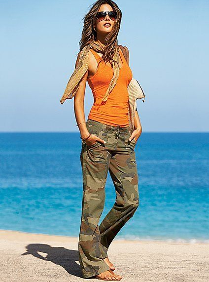Camo pants, orange top, scarf, sunnies. Gorgeous street style. Orange and camo are hot trends.