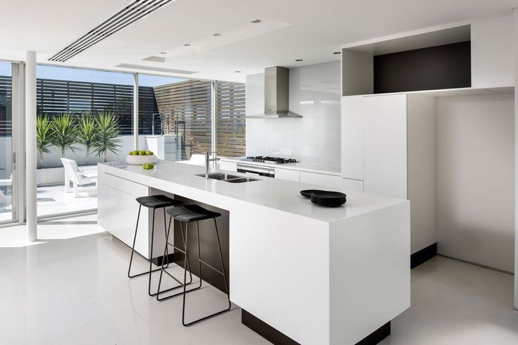 Una casa que conecta el interior con el exterior  Con líneas puras y etéreas la cocina se incorpora sutilmente al ambiente. El inmaculado blanco del mobiliario se contrastó con el negro en los zócalos, los fondos de los estantes y la barra con banquetas Tao (Inclass) a tono Foto:DMAX