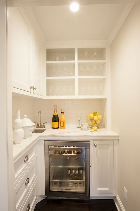 Small, chic butler's pantry features cabinets sans doors lined with wine glasses and martini glasses situated over white lower cabinets fitted with a glass-door wine cooler paired with white marble countertop framing corner bar sink and a white subway tiled backsplash.