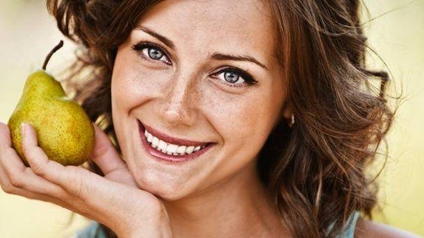 Lächelnde Frau hält eine Birne in der Hand (Quelle: Thinkstock by Getty-Images)