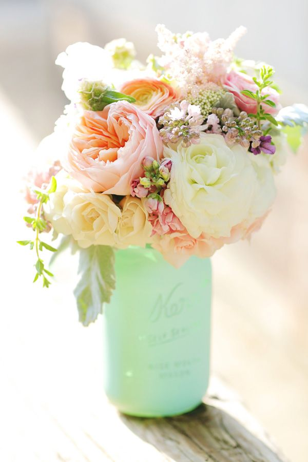 Flowers in jars. Spray paint jam jars yourself and fill with carnations and baby's breath for a vintage wedding
