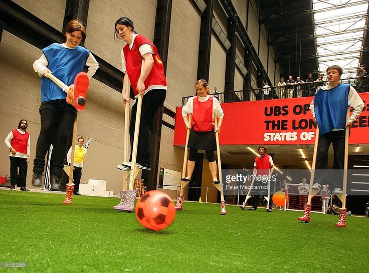 People play stilt football in the Turbine Hall at Tate Modern on May 24, 2008 in London, England. The Turbine Hall has been transformed to house the first realisation of a Fluxolympiad, for which Fluxus artist Larry Miller has programmed a series of Flux-Sports events including soccer played on stilts, obstacle shoe races, slow speed bicycle races, and the balloon shotput, stilt race, slow bicycle race and many more.
