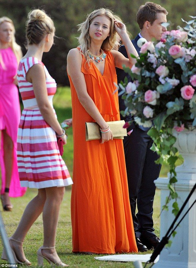 Bright: Kassandra Clementi wore a flowing bright orange maxi dress