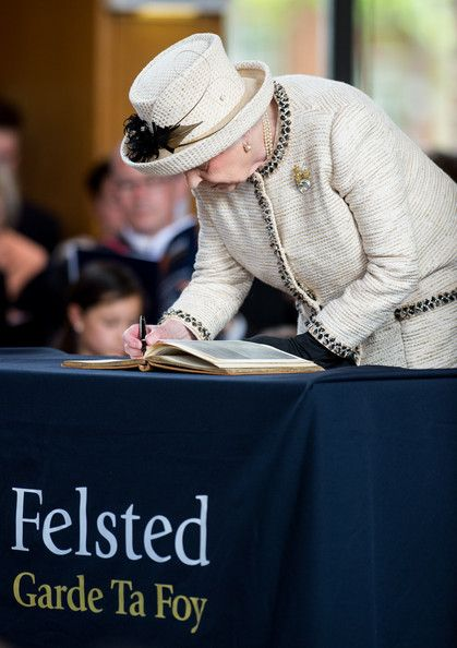 Queen Elizabeth II unveils a plaque during an official visit to Felsted School on May 6, 2014