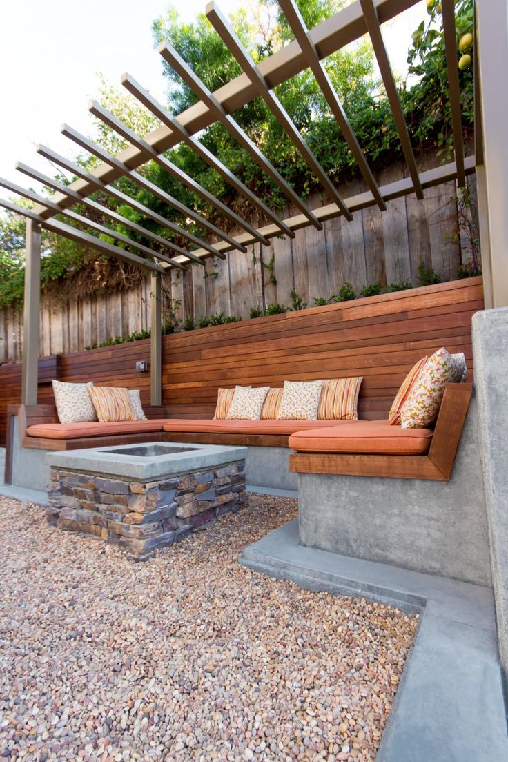 Built-in concrete benches are topped by slatted wood, warming up the space visually while a custom fire pit warms it up physically. A pergola overhead filters light and defines the seating area.