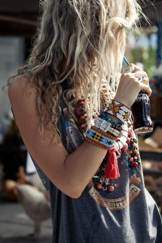 An arm party made up of african bracelets works beautifully with a tattered grunge tee. Mixing genres is everything! Also her lightly dreaded blonde hair is a beautiful haute mess.