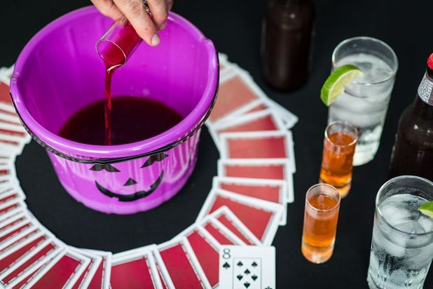 """Fill the Pumpkin: Use a plastic pumpkin that doesn't leak. Spread a deck of cards face down around the pumpkin. Assign different games to different cards. For example, each person who draws a """"jack"""" has to make a dare. Get creative with the rules you set; just remember to set the fours and eights as cards that require the person who draws them to pour a shot-sized portion of their drink into the pumpkin. Anyone who draws the """"ace"""" has to drink whatever is in the pumpkin."""