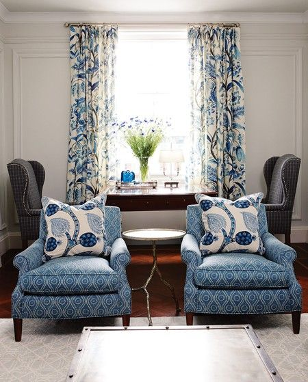 Sophisticated Family Room Seating Area    Achieve a polished look with symmetry.      A skillful mix of patterns infuses this family room with shades of blue, from soft to cerulean. A pair of printed armchairs face the main seating area, while two wing chairs upholstered in menswear-inspired fabric flank a games table.