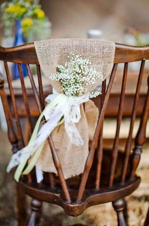 From Grey Likes Wedding, a wonderful wooden chair is decorated with a strip of burlap with tiny flowers wrapped to create the most devine wedding chair decor.