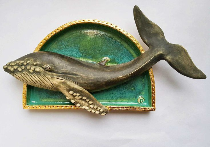 A handmade and sculpted wall piece. Each one of these whale sculptures is handmade and framed in an arch shaped structure, which has a hanging arrangement on the reverse to allow it to be wall mounted. The edge of the arch frame has decorative textures highlighted by an application of gold leaf.