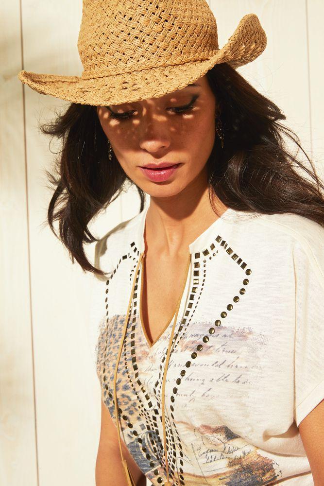 """GRUNGE. Les associations de matières et de décorations pour un look """"cow girl"""" urbaine et branchée. Coupe ample.Manches tombantes chauve-souris. Encolure V avec petit col officier orné d'un passepoil et d'un lien frangé en faux daim. Dessin en sublimation ornée de clous comme un plastron.  Fabriqué en France. #mode#tee-shirt#blanc#elora#country#cow-boy#"""