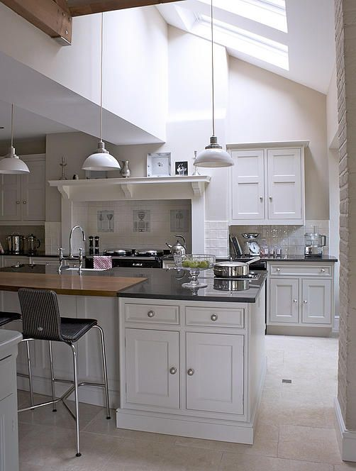 Pendant lights suspended from a vaulted ceiling provide a sense of scale in this classic style bespoke kitchen.