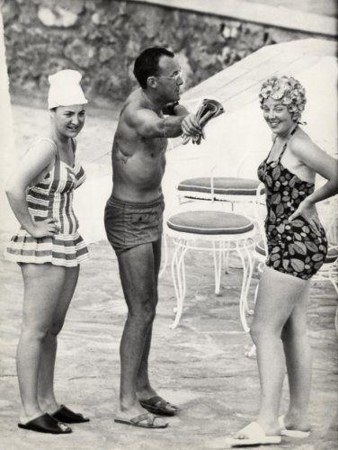 Het koninklijk gezin op vakantie in zwemkleding (badpak, badmuts, zwembroek), [1963]. Vlnr prinses Margriet, prins Bernhard (met het litteken van het auto-ongeluk in 1937 duidelijk zichtbaar) en kroonprinses Beatrix.