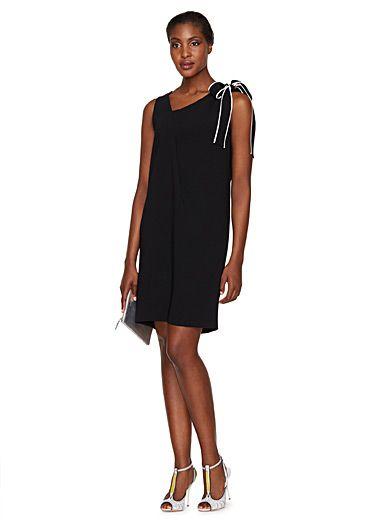 """Classique mode renouvelé chez Boutique Moschino, la petite robe noire affiche une touche graphique irrésistible pour la nouvelle saison. Avec sa boucle soulignée en blanc sur noir et sa coupe au charme rétro, elle vous permettre de jouer la """"lady"""" moderne à la perfection.    Tissage stretch structuré, non doublé   Effet drapé flatteur à l'avant et large ruban liséré à nouer à l'épaule   S'enfile simplement    Le mannequin porte la taille 40"""
