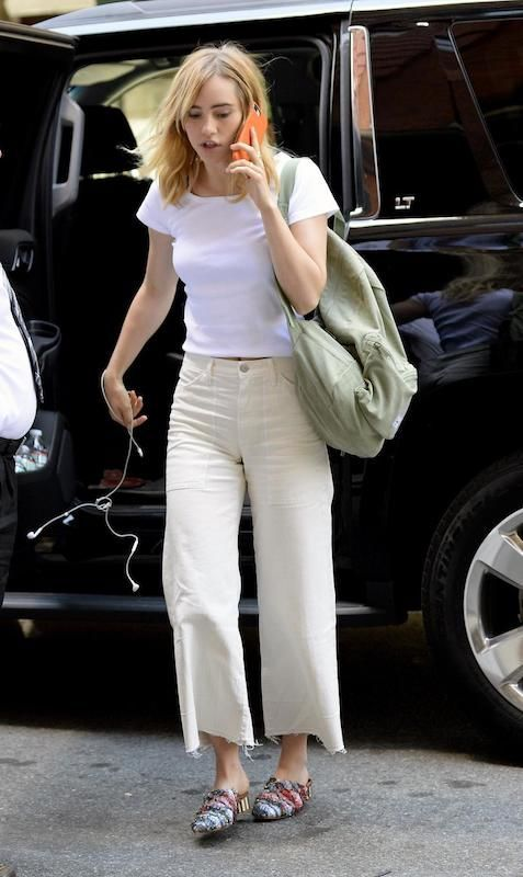 Suki Waterhouse wears cropped kick flared khaki pants, a tight white tee shirt, an oversized green backpack, and embellished multicolored mule shoes