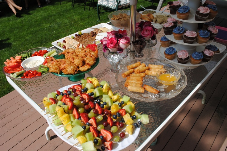 Bridal shower food displayed - fruit skewers, coconut shrimp, veggie trays, cheese trays, dips, cupcakes