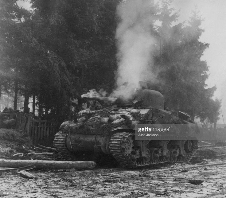 A blazing Sherman tank abandoned during the Battle of the Bulge and fight for the Belgian town of Manhay.