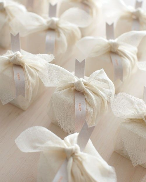 """Classic sugar-coated almond gifts, which signify fertility in many cultures, get a makeover when standard-issue tulle wrapping is traded in for loosely woven linen. To make, place the nuts in a small box, wrap with a square of fabric, and tie the corners into a knot. Slip in an """"enjoy"""" banner to finish. Crossings dragees (800-209-6141). Clear-Bags """"Crystal Clear Boxes"""" PLB104. Grayline Fabrics open-weave linen in color 3."""