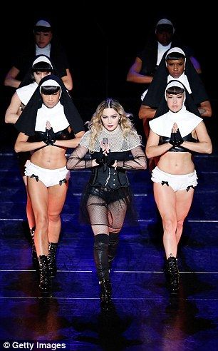 Madonna is flanked by scantily clad dancers as she performs in Sydney on her Rebel Heart tour