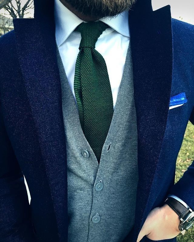 Rock a navy wool blazer with a grey sweater vest for a classic and refined silhouette.   Shop this look on Lookastic: https://lookastic.com/men/looks/blazer-sweater-vest-dress-shirt/22872   — White Dress Shirt  — Dark Green Knit Tie  — Grey Sweater Vest  — White Pocket Square  — Navy Wool Blazer