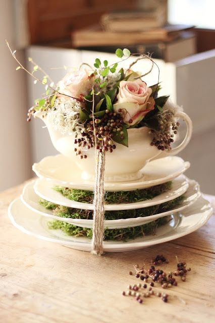 Tea cup and saucer arrangement with sweetheart roses and moss.