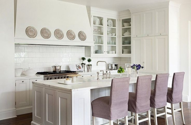 Lavender slipcover upholstery on the barstools provides the sole moment of color in Suzanne Kasler's kitchen, while a simple display of pewter plates adds a graphic hit to the feminized space and breaks up the sea of white.