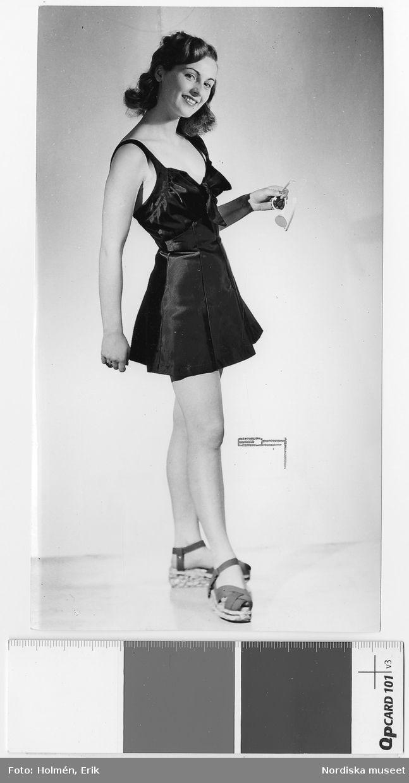 """Från utställningen """"Kalifornia"""", 1947. Modell i kort klänning, solglasögon i handen och platåskor. Nordiska Kompaniet. Fotograf: Erik Holmén"""