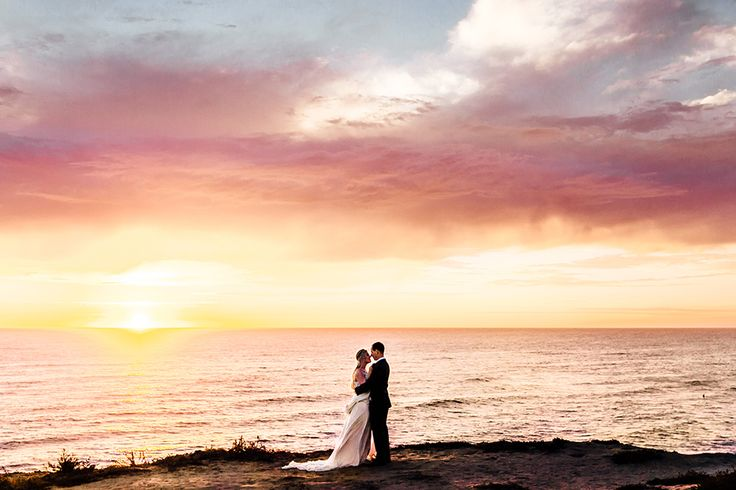 San diego bohemian wedding shoot at sunset cliffs bride chiffon gown with ruffles and thin straps with low back design and plunging neckline and flower headpiece decor with groom charcoal grey suit with matching vest and white dress shirt with long teal tie kissing at sunset