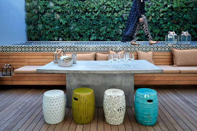 The wooden pool deck morphs into seating along the length of the lap pool. The cushions are covered in Hertex fabric. The Sempre dining table and pottery stools are from Weylandts, and the pool tiles from Moroccan Warehouse.