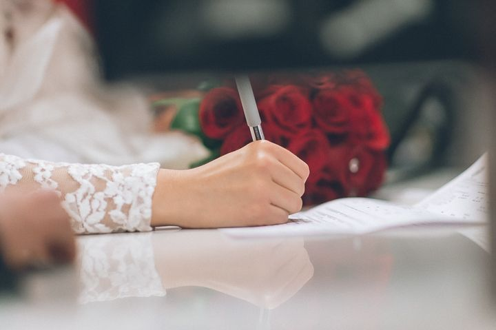 Couple signs their papers at the NYC Marriage Bureau. Captured by NYC City Hall Wedding Photographer Ben Lau.