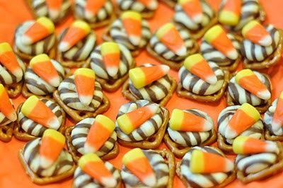 pretzels snaps, hershey's kiss, candy corn... place kiss on pretzel, microwave then stick candy corn on top.  Yum, yum!  Try it with a Rollo candy instead with a pecan on top as another option.