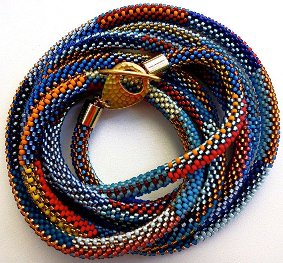 Long and beautiful fancy beaded rope. Fusion patchwork contains 40 unique segments. Made of more than 20 shades of blue, red and orange. Suitable for everyday use and for special occasions. Original and elegant, perfect gift for stylish person. Soft and flexible, any knots can be tied. Can be a necklace or a bracelet  ♦ Necklace Length: ≈165 cm | 65 ♦ Necklace Diameter: 6,5mm | 1/4 ♦ Technique: bead crochet ♦ Materials: premium Japanese glass beads (size 11/0), nylon thread ♦ TierraCast…