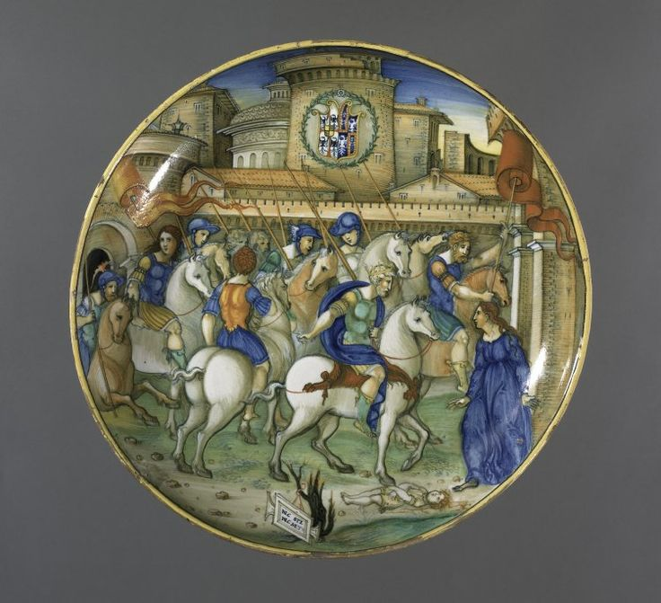 """Dish or bowl on low foot. Earthenware covered front and back with presumed tin glaze. Painted with soldiers riding through a town. To the right a woman gesturing to Trajan (on horseback, crowned); between them her dead child. Centre background is a shield of arms - Gonzaga impaling Este, for Isabella d'Este, Marchioness of Mantua. At the bottom, a tablet lettered """"NEC SPE NEC METU"""". Subject mentioned in Dante."""