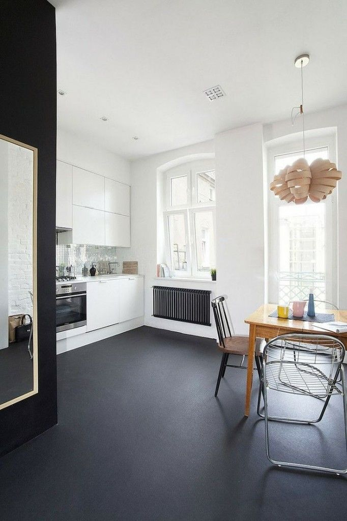 The black floor really anchors this space and gives it some drama. Add a large wall mirror to bounce the light around and plenty of wood for warmth