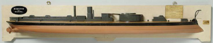 anoniem | Halfmodel van een rammonitor, attributed to Rijkswerf Amsterdam, 1867 - 1869 | Gepolychromeerd halfmodel (stuurboord) en blokmodel van een monitor. Het heeft een verticale voorsteven met kipstut, een scherp achterschip, roer met afgerond roerblad; een schroefas van een paar. De originele geschutskoepel ontbreekt; op dek tien smalle dekhuizen en kasten: op de dekopbouw net achter de koepel een brug met roosters dwarsscheeps en een schoorsteen. Op een dekopbouw achter het stuurwiel…
