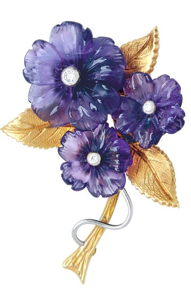 An Amethyst and Diamond Brooch  Designed as a blossoming branch with a trio of carved amethysts centered by small round diamonds, to textured leaves and stem, with a polished curving tendril, mounted in 14k yellow and white gold