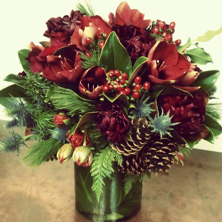 Holiday Arrangement filled with Peonies and Amaryllis accented with hypericum berries, tulips, winter greens and pine cones.