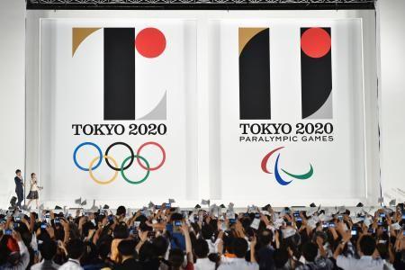 東京都庁舎前で開かれたイベントで発表された、2020年東京五輪(左)とパラリンピックの公式エンブレム=24日夜 ▼24Jul2015共同通信|五輪公式エンブレム発表 東京の「T」、多様性の黒 http://www.47news.jp/CN/201507/CN2015072401001759.html