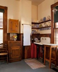 An old icebox adds some storage to a kitchen too old to have offered much capacity. Note the unfitted tables and open shelves.