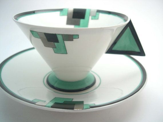 Beautiful Art Deco tea cup and saucer from Shelley. Handpainted design, green, silver and black. Shape: Vogue C. 1925 - 1945 Cup measures: 2 1/2 high & Saucer measures 5 1/2 across Very good conditon, no chips, no cracks, no crazing, no hairlines, no stains and both pieces ring #artdeco