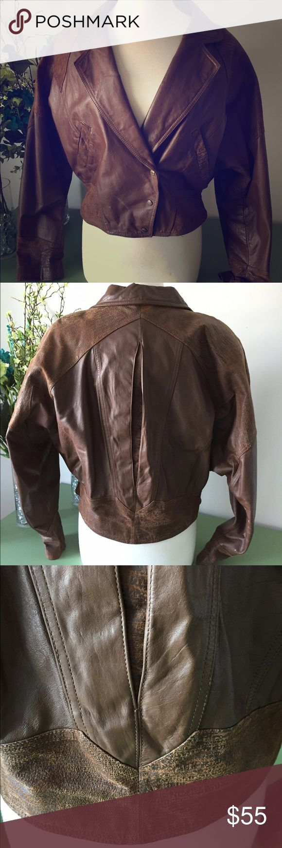 G4000 GENUINE LEATHER JACKET This G4000 Genuine Leather Vintage Jacket will fit perfectly in with the rest of your trendy wardrobe!  ☞ Vintage 1980s style ☞ Mixed leather medium-tone brown color ☞ Wide lapel with asymmetrical 3-snap button front closure ☞ Inverted gusset on back with topstitched diamond design  ☞ 1980s raglan style sleeves ☞ 2 waist pockets ☞ In great condition overall. Some minor wear and tear. ☞ Cropped Moto Style: Very roomy though the shoulders and sleeves, tapered…