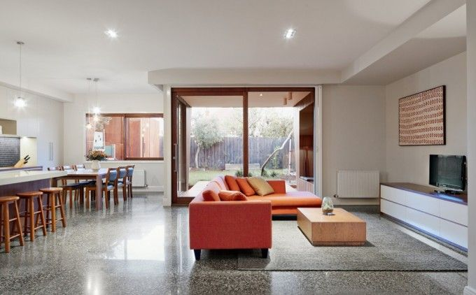Orange Sofa With L Shape Design In Beautiful Open Plan Interior Including Living Room And Dining Room Also Kitchen With Grey Marble Floor Tiles And Grey Rug Plus White Countertop Also Wooden Dining Table With Glass Door