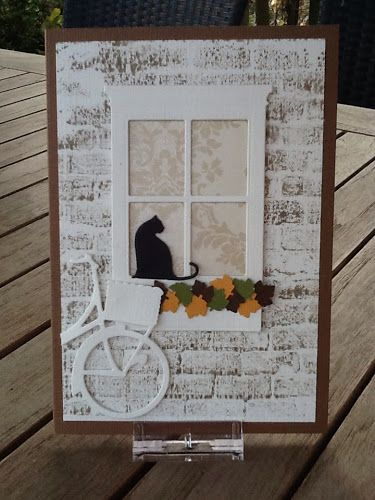By Karine. Background stamped in white ink using a brick wall stamp. Small Madison window, window box, bicycle, & cat die-cuts, all by Memory Box. Leaves probably punched. Mounted on brown card base.