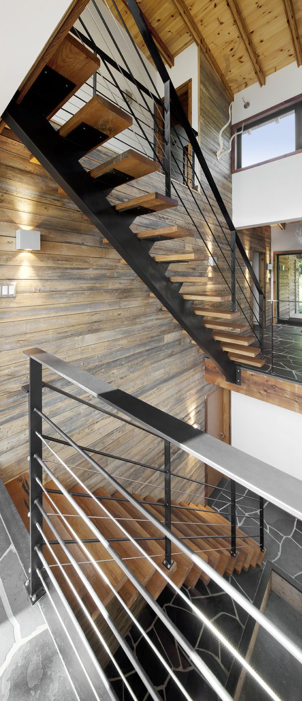 Escalier en bois et métal qui dessert deux niveaux dans cette maison design.