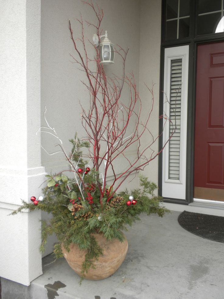 Christmas outdoor urn. Made with greenery clippings from the yard, birch branches paint red, sugar pine cones, and a few Christmas balls wired onto the branches.